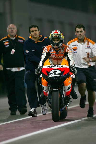 2008 MotoGP. Losail, Qatar. 7th - 9th March 2008. Rd 1. Dani Pedrosa, Honda, 3rd position, is pushed down the pit lane after running out of fuel, action. World Copyright: Martin Heath/LAT Photographic. Ref: Digital Image Only.