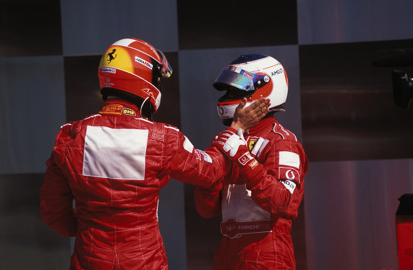 Michael Schumacher and Ferrari team-mate Rubens Barrichello celebrate in parc ferme after the race.