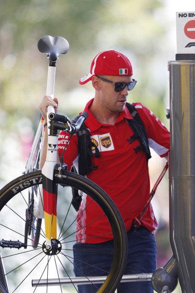 Sebastian Vettel, Ferrari, enters the paddock carrying a bicycle.