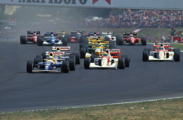Riccardo Patrese, Williams FW14B Renault, leads Ayrton Senna, McLaren MP4-7A Honda, Nigel Mansell, Williams FW14B Renault (directly behind Patrese), Gerhard Berger, McLaren MP4-7A Honda, and Michael Schumacher, Benetton B192 Ford, into the first corner at the start of the race.