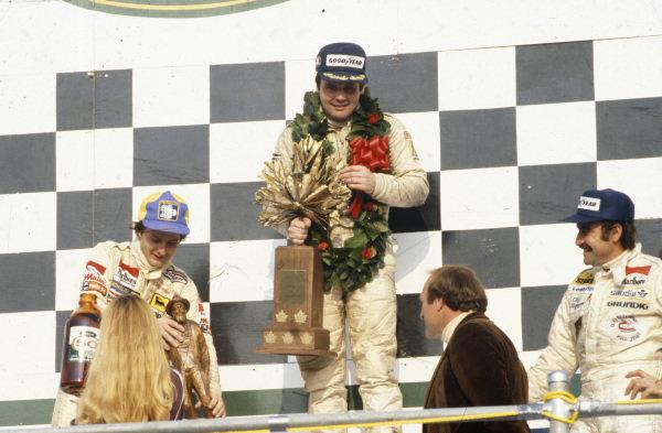 Alan Jones celebrates victory on the podium Gilles Villeneuve, 2nd position, and Clay Regazzoni, 3rd position.