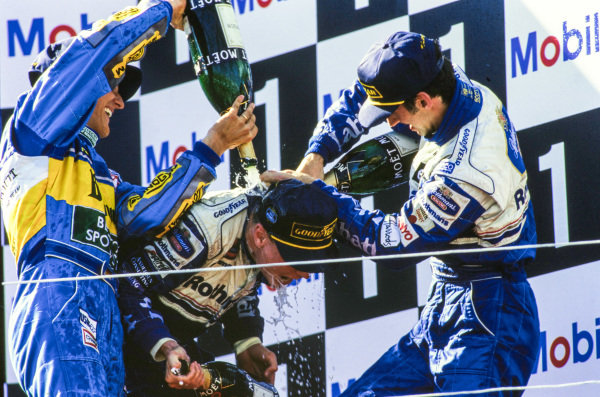 Michael Schumacher, 2nd position, and Damon Hill, 3rd position, douse David Coulthard, 1st position, with champagne on the podium.