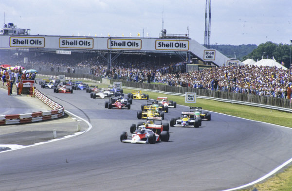 Alain Prost, McLaren MP4-3 TAG, leads Nelson Piquet, Williams FW11B Honda, Nigel Mansell, Williams FW11B Honda, Teo Fabi, Benetton B187 Ford, Ayrton Senna, Lotus 99T Honda, Thierry Boutsen, Benetton B187 Ford, Stefan Johansson, McLaren MP4-3 TAG, and Michele Alboreto, Ferrari F1-87, into Copse at the start.