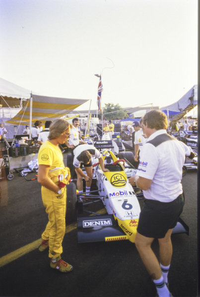 Keke Rosberg stands in front of his Williams FW09 Honda, as mechanics work on it.