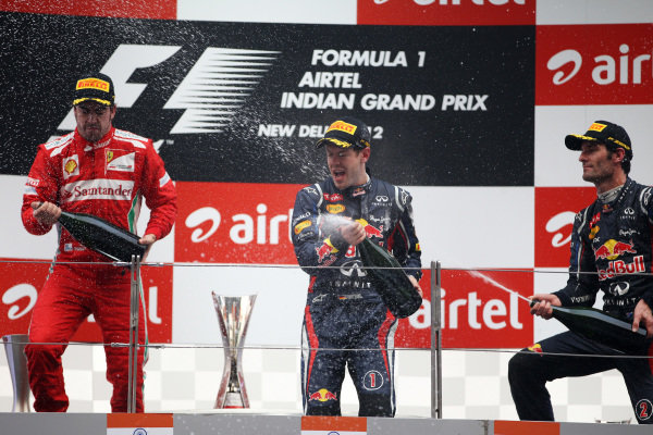 (L to R): Fernando Alonso (ESP) Ferrari, Sebastian Vettel (GER) Red Bull Racing and Mark Webber (AUS) Red Bull Racing celebrate with the champagne on the podium. Formula One World Championship, Rd17, Indian Grand Prix, Buddh International Circuit, Greater Noida, New Delhi, India, Race, Sunday 28 October 2012.
