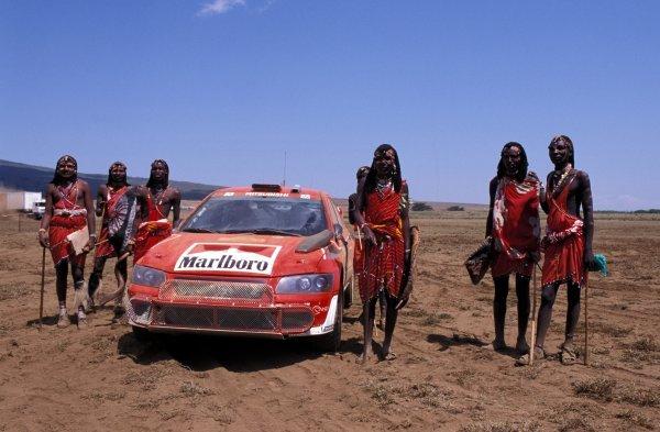 Kenyan rally fans pose with Alister McRae's (GBR) Mitsubishi Lancer WRC.FIA World Rally Championship, Rd8, Safari Rally, Kenya. 12-14 July 2002.BEST IMAGE