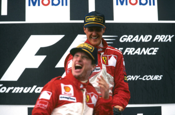 Magny-Cours, France. 27-29 June 1997. Michael Schumacher (Ferrari) 1st position, sprays his teammate Eddie Irvine (Ferrari) on the podium, portrait.  World Copyright: LAT Photographic. Ref:  97 FRA 11.