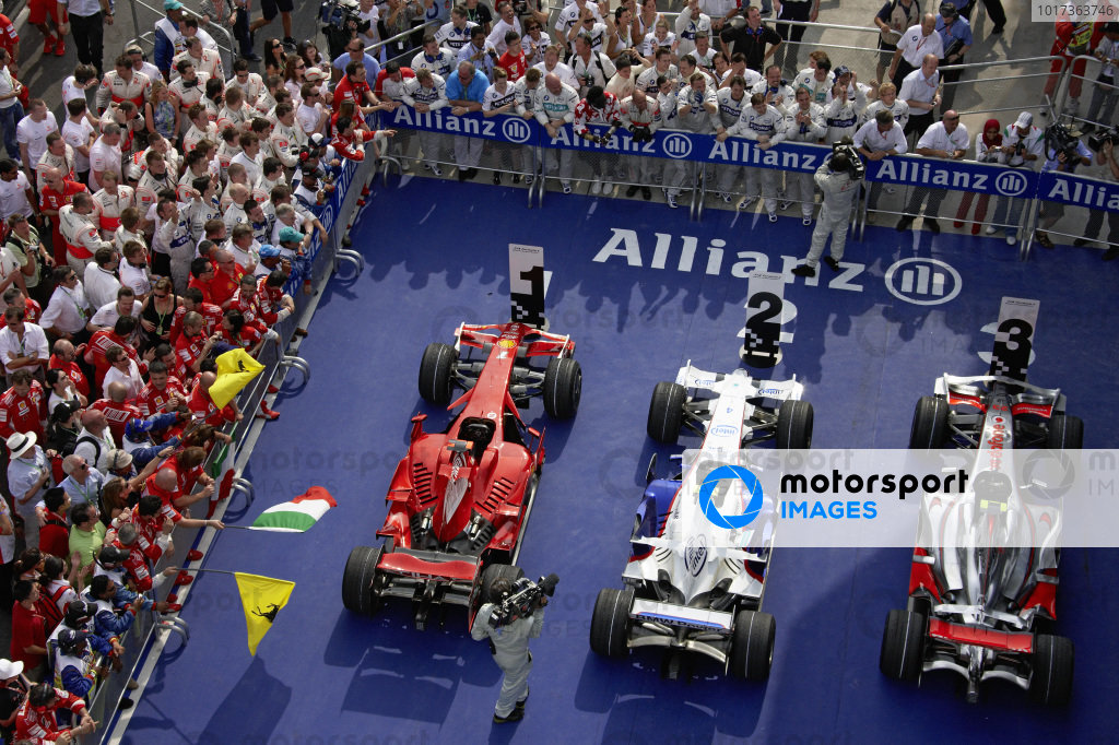 The teams line up around parc ferme to congratulate their drivers.
