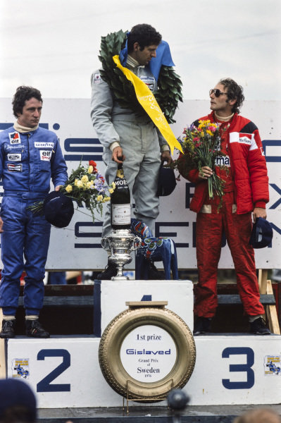 Jody Scheckter celebrates victory with teammate Patrick Depailler, 2nd position and Niki Lauda, 3rd position.