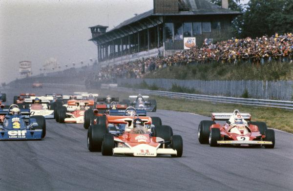 James Hunt, McLaren M23 Ford, leads Clay Regazzoni, Ferrari 312T2, Patrick Depailler, Tyrrell P34, Jody Scheckter, Tyrrell P34, and the rest of the field at the restart.