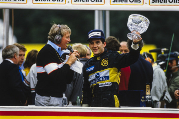 Ayrton Senna, 2nd position, lifts his trophy as he is interviewed on the podium.