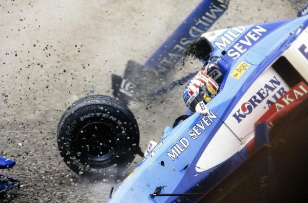 Alexander Wurz, Benetton B198 Playlife, flies through the air and kicks up a substantial amount of gravel as he barrel rolls.