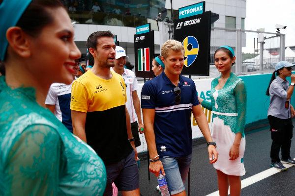 Sepang International Circuit, Sepang, Malaysia. Sunday 01 October 2017. Jolyon Palmer, Renault Sport F1, and Marcus Ericsson, Sauber, walks through a corridor of grid girls. World Copyright: Andy Hone/LAT Images  ref: Digital Image _ONY4445