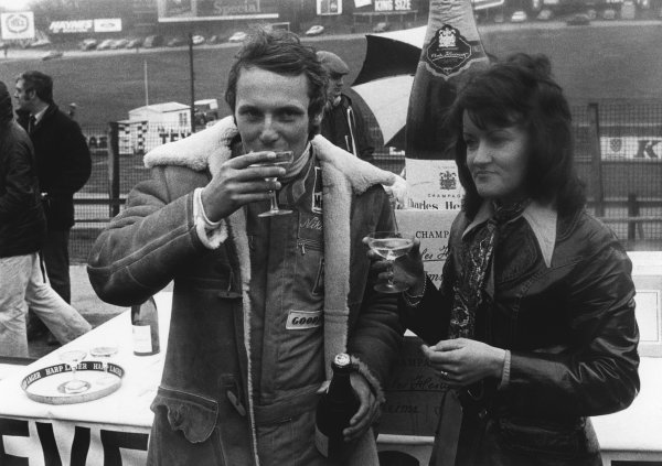 Brands Hatch, England. 17th March 1974. Niki Lauda (Ferrari 312B3), 2nd position, drinks a glass of 100 bottles of Champagne given to the fastest lap of the day. This is Friday's practice winner, portrait. World Copyright: LAT Photographic. Ref: B/W Print.