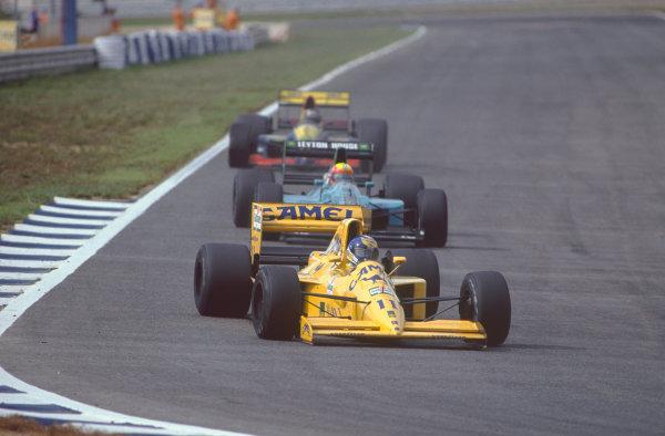 Estoril, Portugal. 21st - 23rd September 1990. Derek Warwick (Lotus 102-Lamborghini), retired, leads Mauricio Gugelmin (Leyton House CG901-Judd), 12th position, action.  World Copyright: LAT Photographic. Ref:  90POR16.