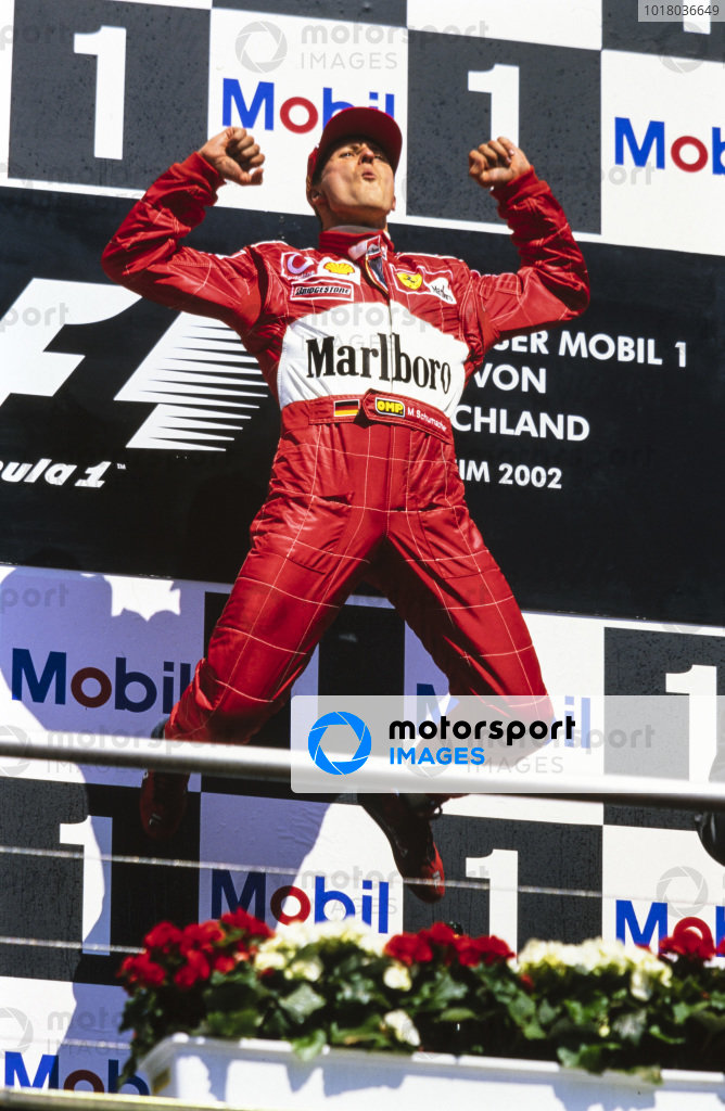 Michael Schumacher, 1st position, celebrates victory with a leap on the podium.