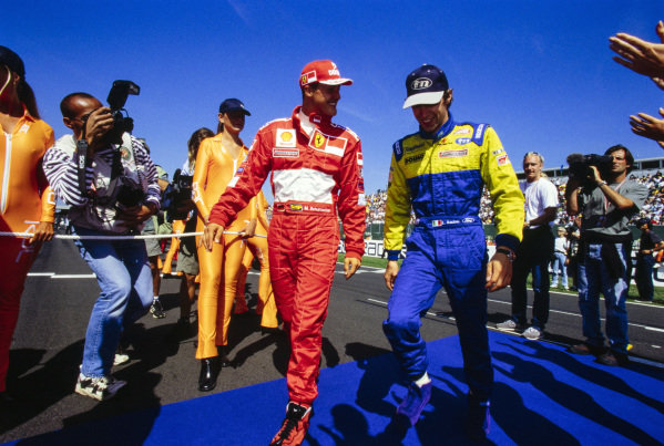Michael Schumacher chats with Luca Badoer.