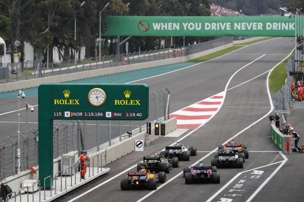 Carlos Sainz Jr., McLaren MCL34, Lewis Hamilton, Mercedes AMG F1 W10, Valtteri Bottas, Mercedes AMG W10, Nico Hulkenberg, Renault R.S. 19, Daniil Kvyat, Toro Rosso STR14, and Lando Norris, McLaren MCL34, queue to leave the pits