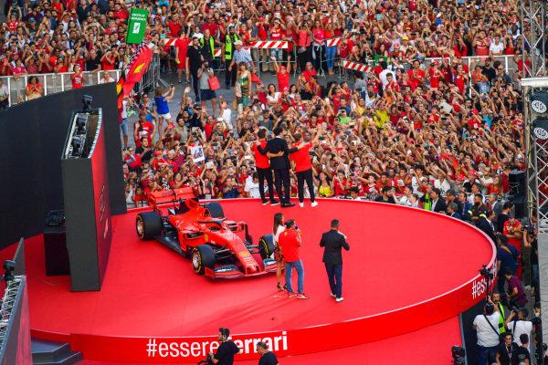 Charles Leclerc, Ferrari, Mattia Binotto, and Sebastian Vettel, Ferrari stand on the stage in front of the crowd