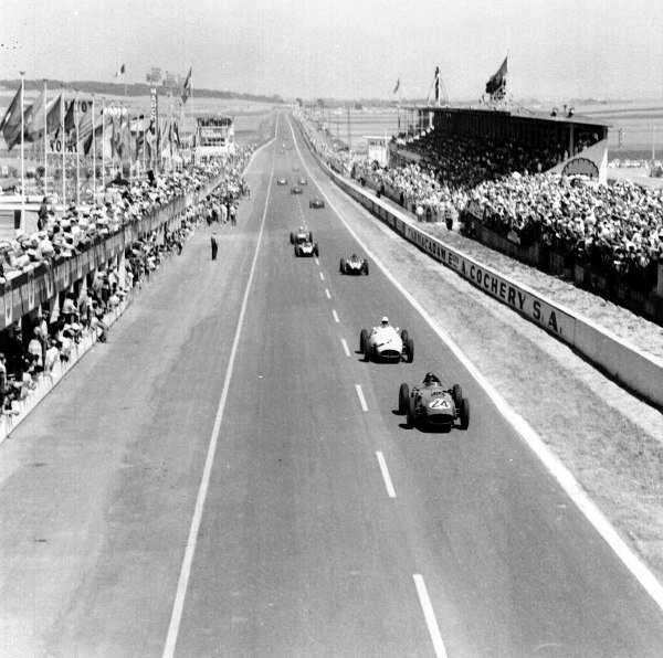 1959 French Grand Prix.Reims, France.3-5 July 1959.Tony Brooks (Ferrari Dino 246) leads Stirling Moss (BRM P25) and the field past the grandstands and pits.Ref-4399.World Copyright - LAT Photographic