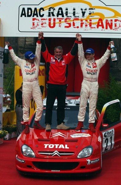(L-R) Daniel Elena (FRA), Citroen team manager Guy Frequelin (FRA) and Sebastien Loeb (FRA) celebrate victory on the podium.Fia World Rally Championship, Rd10, Rallye Deutschland, Germany, Leg 3, 25 August 2002.DIGITAL IMAGE