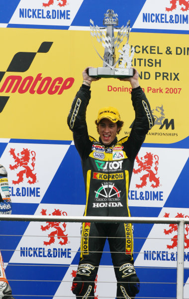 2007 MotoGP. British Grand Prix.  Donington Park, England. 22nd-24th June 2007.  250cc. Andrea Dovizioso, Honda, 1st position, celebrates with the trophy on the podium.  Ref: IMG_5945a. World Copyright: LAT Photographic