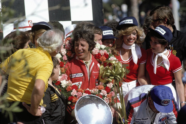 Mario Andretti, 1st position, celebrates on the podium.