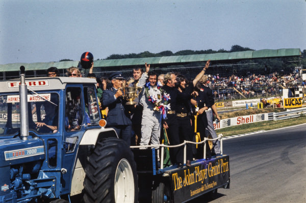 Emerson Fittipaldi and Lotus owner Colin Chapman celebrate victory with team on the back of a trailer being towed by a tractor.