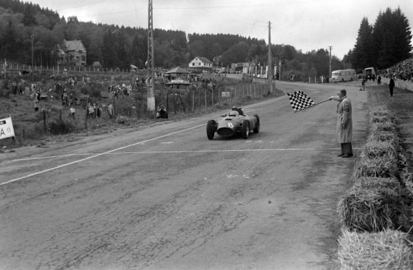 Peter Collins, Ferrari D50, crosses the line to win the race.