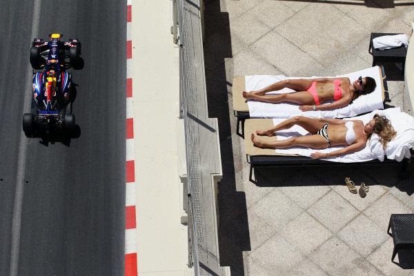 Sebastian Vettel (GER) Red Bull Racing RB7 passes Linn Gothall (SWE) British Airways senior first officer and Shirin, British Airways stewardess sunbathing. Formula One World Championship, Rd 6,  Monaco Grand Prix, Qualifying Day, Monte-Carlo, Monaco, Saturday 28 May 2011.