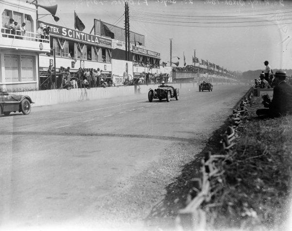 Freddie Dixon / Cyril Paul, Riley Ltd., Riley 6/12 MPH Racing leads Frank Stanley Barnes / Alf Langley, Singer Le Mans 1.5L, past the pits.