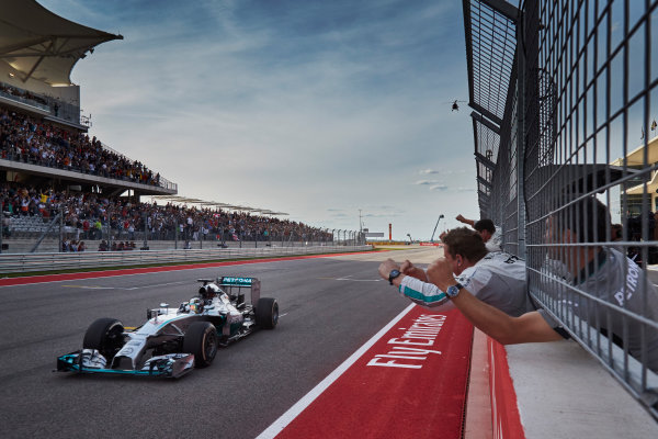 Circuit of the Americas, Austin, Texas, United States of America. Sunday 2 November 2014. Lewis Hamilton, Mercedes F1 W05 Hybrid passes the pits as his team cheer from the pit wall as he wins the race. World Copyright: Steve Etherington/LAT Photographic. ref: Digital Image SNE24852