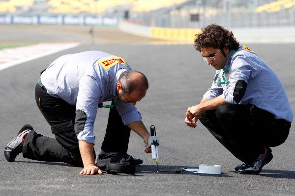 Korea International Circuit, Yeongam-Gun,South Korea.13st October 2011.Pirelli staff members take readings from the track.World Copyright:Charles Coates/LAT Photographicref: Digital Image _X5J9672