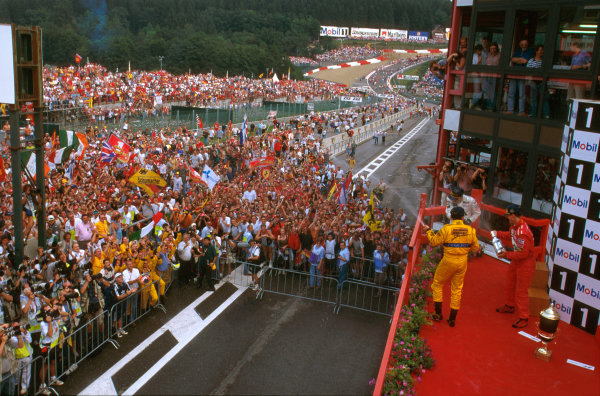 Spa-Francorchamps, Belgium.22-24 August 1997.Michael Schumacher (Ferrari ) 1st position, Giancarlo Fisichella (Jordan) 2nd position and Mika Hakkinen (McLaren) 3rd position but later disqualified on fuel irregularities, celebrate on the podium in front of the fans.Ref-97 BEL 07.World Copyright - LAT Photographic