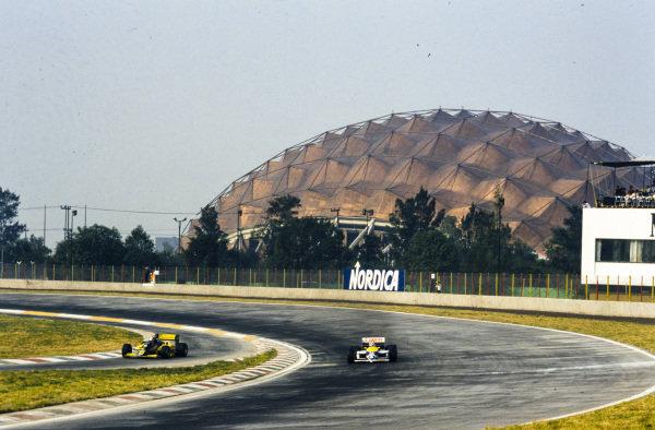 Nelson Piquet, Williams FW11 Honda, rounds Peraltada as Alessandro Nannini, Minardi M/85B Motori Moderni, enters the pits.
