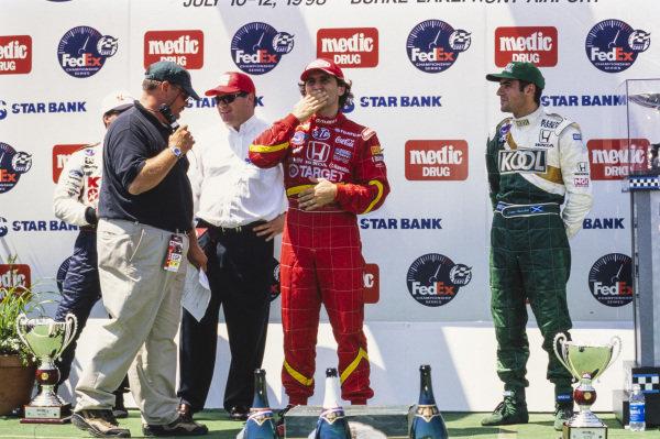 Alex Zanardi blows a kiss to the crowd on the podium. Also present is Michael Andretti, Chip Ganassi and Dario Franchitti.