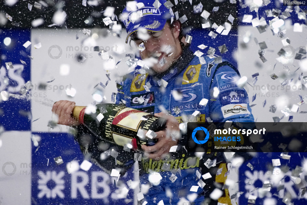 Fernando Alonso celebrates becoming world champion as the confetti rains down on the podium.