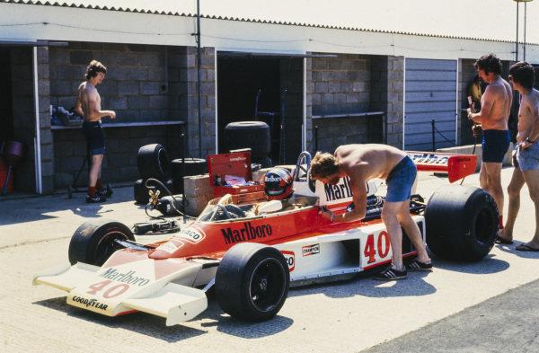 Mechanics work on Gilles Villeneuve's McLaren M23 Ford in the pitlane.