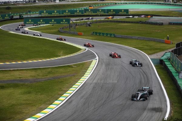 Lewis Hamilton, Mercedes AMG F1 W09, leads Valtteri Bottas, Mercedes AMG F1 W09, Sebastian Vettel, Ferrari SF71H, Kimi Raikkonen, Ferrari SF71H, Max Verstappen, Red Bull Racing RB14 Tag Heuer, and the rest of the pack.