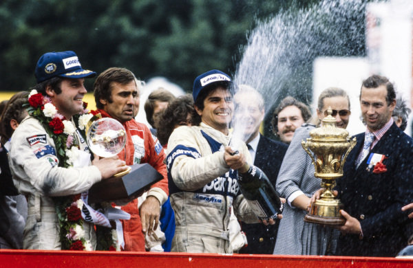 Nelson Piquet, 2nd position, celebrates on the podium. Alan Jones, 1st position, and Carlos Reutemann, 3rd position, look on.