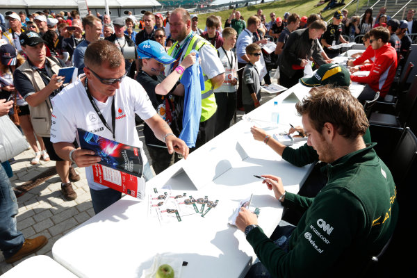 Silverstone, Northamptonshire, England 29th June 2013 Giedo van der Garde, Caterham F1, and Charles Pic, Caterham F1, sign autographs for fans World Copyright: Charles Coates/  ref: Digital Image _N7T2430