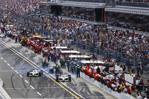Tony Kanaan, Andretti Green Racing, Dallara IR-03 Honda, leaves the pits narrowly in front of Michael Andretti, Andretti Green Racing, Dallara IR-03 Honda.