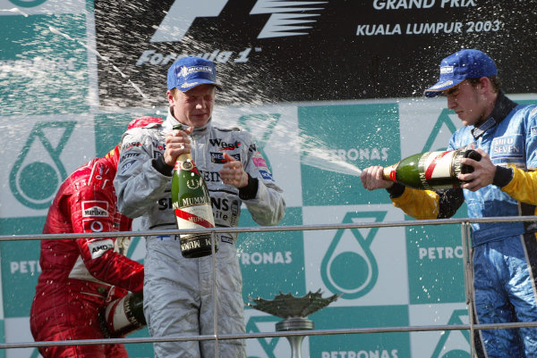 2003 Malaysian Grand Prix. Sepang, Kuala Lumpur, Malaysia.21-23 March 2003.Kimi Raikkonen (McLaren Mercedes) 1st position gets a spraying of champagne from Rubens Barrichello (Ferrari) 2nd position and Fernando Alonso (Renault) 3rd position, on the podium.World Copyright - Steve Etherington/LAT Photographic ref: Digital Image Only