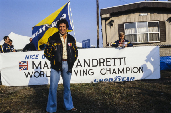Mario Andretti stands in front of a banner congratulating him on his championship victory.
