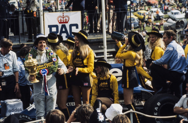 Jody Scheckter celebrates victory on the podium as one of the JPS girls enjoys some of the winner's champagne.