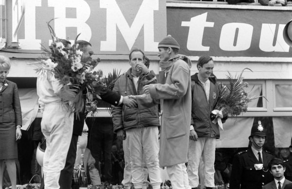 Henry Ford II congratulates Ken Miles, 2nd position, while teammate Denny Hulme enjoys a glass of champagne on the podium.