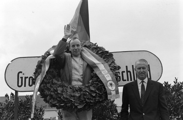 John Surtees, 1st position, celebrates on the podium.