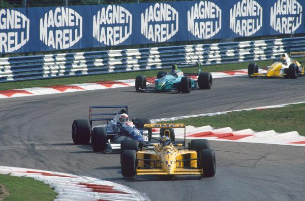 Monza, Italy. 7 - 9 September 1990. Derek Warwick (Lotus 102-Lamborghini), retired, leads Saturo Nakajima (Tyrrell 019-Ford), 6th position, action.  World Copyright: LAT Photographic. Ref:  90ITA25.