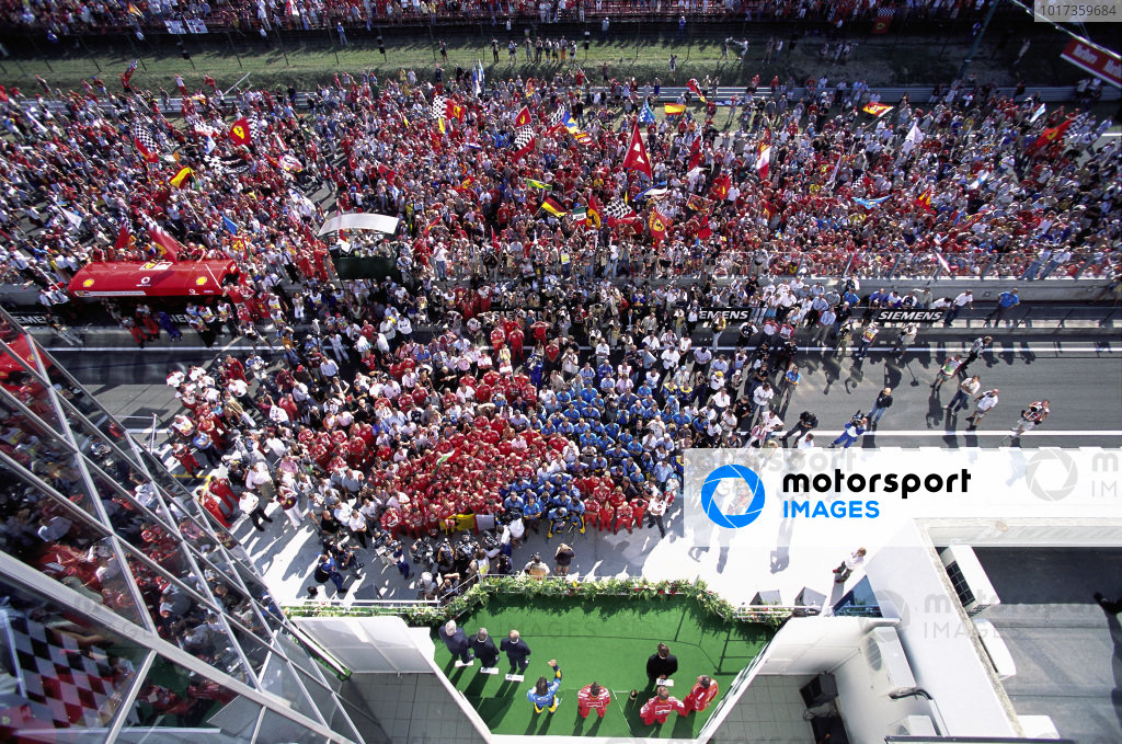 Fans and teams swarm the track for the podium ceremony.