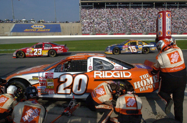 Leader Tony Stewart makes a early pit stop as Hut Stricklin and Michael Waltrip speed by on pit road. Note hockey helmets worn by the front wheel changer and jack man.